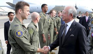Malaysian Prime Minister Najib Razak, right, greets a Royal Australian Air Force P-3 Orion captain Lt. Russell Adams and his crew involved in the search for wreckage and debris of the missing Malaysia Airlines MH370 in Perth, Australia, Thursday, April 3, 2014.Najib was in Australia to meet with Australian Prime Minister Tonny Abbott to hold bilateral talks about the missing plane and to attend briefings with crew members. (AP Photo/Rob Griffith, Pool)