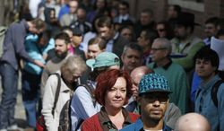 ** FILE ** In this Thursday March 13, 2014, file photo, job seekers line up to attend a marijuana industry job far in Downtown Denver. (AP Photo/Brennan Linsley, File)