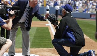 Los Angeles Dodgers broadcaster Vin Scully, left, throws the ceremonial first pitch to former Los Angeles Dodgers pitcher Sandy Koufax before a baseball game between the Los Angeles Dodgers and the San Francisco Giants on Friday, April 4, 2014, in Los Angeles. (AP Photo/Jae C. Hong)