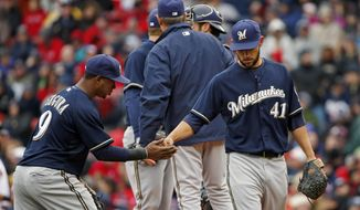 Milwaukee Brewers starting pitcher Marco Estrada (41) receives a handshake from shortstop Jean Segura (9) as he is relieved in the sixth inning of a baseball game against the Boston Red Sox at Fenway Park in Boston, Friday, April 4, 2014. (AP Photo/Elise Amendola)