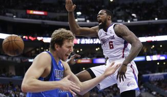 Los Angeles Clippers' DeAndre Jordan, right, screams after making a dunk in front of Dallas Mavericks' Dirk Nowitzki during the first half of an NBA basketball game Thursday, April 3, 2014, in Los Angeles. (AP Photo/Jae C. Hong)