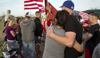Fort Hood soldiers Alyssa Jackson and her husband, C.J. Jackson, embrace after participating in a tribute walk for the victims of Wednesday's shooting at Fort Hood, at Lions Club Park in Killeen, Texas, on Friday, April 4, 2014. (AP Photo/Austin American-Statesman, Jay Janner)