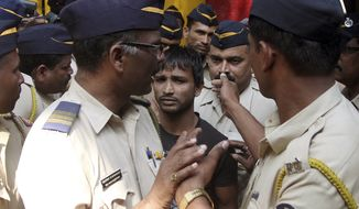 Police officials escort one of the four convicts in a gang rape case to a court in Mumbai, India, Friday, April 4, 2014. An Indian court on Friday sentenced to death three men who raped a photojournalist inside an abandoned textile mill in the financial hub of Mumbai last year. A fourth defendant was sentenced to life in prison, Nikam said. (AP Photo)