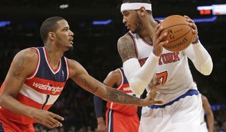 Washington Wizards' Trevor Ariza (1) defends New York Knicks' Carmelo Anthony (7) during the first half of an NBA basketball game Friday, April 4, 2014, in New York. (AP Photo/Frank Franklin II)