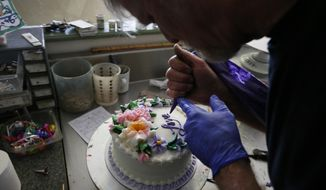 In this March 10, 2014, photo, Masterpiece Cakeshop owner Jack Phillips decorates a cake inside his store, in Lakewood, Colo. (AP Photo/Brennan Linsley) ** FILE **