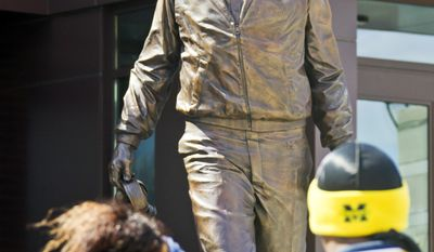Michigan fans take photos beside a newly unveiled statue of former coach Bo Schembechler, outside the newly renovated football training facility also bearing his name, before the football team's annual spring game, Saturday, April 5, 2014, in Ann Arbor, Mich. (AP Photo/Tony Ding)
