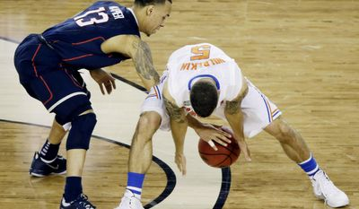 Connecticut guard Shabazz Napier (13) and Florida guard Scottie Wilbekin (5) reach for a loose ball during the second half of the NCAA Final Four tournament college basketball semifinal game Saturday, April 5, 2014, in Arlington, Texas. (AP Photo/Tony Gutierrez)