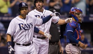 Tampa Bay Rays' James Loney, left, and Matt Joyce, center, head to the dugout past Texas Rangers catcher Robinson Chririnos, right, after Joyce's two-run home run during the fourth inning of a baseball game on Saturday, April 5, 2014, in St. Petersburg, Fla. (AP Photo/Steve Nesius)