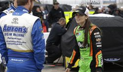 Danica Patrick, right, talks with fellow drivers before qualifications for the NASCAR Sprint Cup Series auto race at Texas Motor Speedway in Fort Worth, Texas, Saturday, April 5, 2014. (AP Photo/LM Otero)