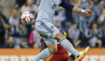 Sporting Kansas City forward Dom Dwyer, top, plays the ball over Real Salt Lake defender Abdoulie Mansally, bottom, during the first half of an MLS soccer match in Kansas City, Kan., Saturday, April 5, 2014. (AP Photo/Orlin Wagner)