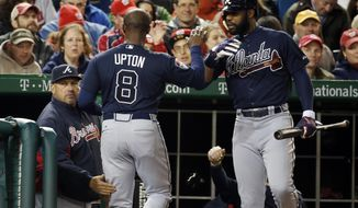 Atlanta Braves' Justin Upton (8) celebrates after scoring, with manager Fredi Gonzalez, left, and Jason Heyward during the fourth inning of a baseball game against the Washington Nationals at Nationals Park Saturday, April 5, 2014, in Washington. Upton scored on a throwing error by Nationals third baseman Ryan Zimmerman. (AP Photo/Alex Brandon)