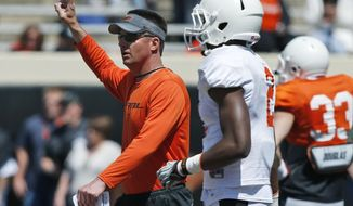 Oklahoma State head coach Mike Gundy directs an Orange Blitz NCAA college spring football practice in Stillwater, Okla., Saturday, April 5, 2014. (AP Photo/Sue Ogrocki)