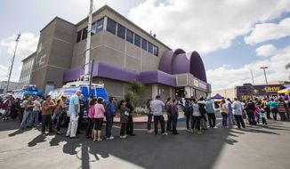 **FILE** Applicants line up outside the SEIU-UHW office during a health care enrollment event in Commerce, Calif., on March 31, 2014. (Associated Press)