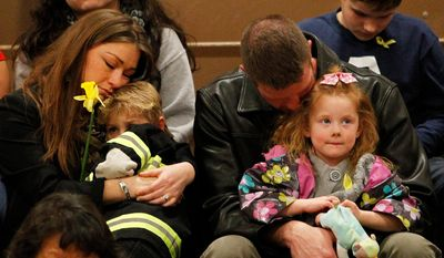 Kelly and Dane Brooks of Arlington hold their children Logan, 6, and Gwendolyn, 4, during a prayer service hosted by the Arlington Ministerial Association in honor of those affected by the Oso mudslide, at Haller Middle School on Friday, April 4, 2014. (AP Photo/POOL, Genna Martin)