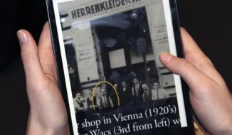 In this Jan. 27, 2014 photo provided by Jane Rohman, an image on a tablet screen at the Simon Wiesenthal Museum of Tolerance in New York, showing Moritz Wacs, circled, posing for a photo with others in Vienna, Austria in the 1920's. University of New Haven students are working on a daunting assignment: Who was the suspected Nazi who protected Wacs and his Jewish family 75 years ago from violence, and warned them to flee Austria just before World War II broke out? (AP Photo/Jane Rohman)