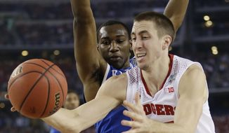 Wisconsin guard Josh Gasser, right, drives to the basket past Kentucky guard Dominique Hawkins during the first half of an NCAA Final Four tournament college basketball semifinal game Saturday, April 5, 2014, in Arlington, Texas. (AP Photo/David J. Phillip)