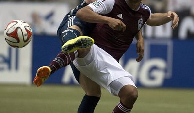 Vancouver Whitecaps FC Jordan Harvey fights for control of the ball with Colorado Rapids FC Gabriel Torres during first half of MLS soccer action in Vancouver, Canada, Saturday, April 5, 2014. (AP Photo/The Canadian Press, Jonathan Hayward)