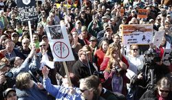 Gun rights activists hold signs during a rally at the Empire State Plaza on Tuesday, April 1, 2014, in Albany, N.Y. With the deadline falling April 15 for registering AR-15s and other guns newly classified as assault weapons, some Second Amendment advocates are calling for civil disobedience and ignoring the new law. (AP Photo/Mike Groll)