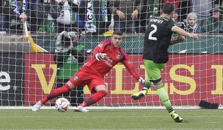 Seattle Sounders midfielder Clint Dempsey, right, scores on a penalty kick to tie the game against Portland Timbers goalkeeper Andrew Weber late in the second half of an MLS soccer game in Portland, Ore., Saturday, April 5, 2014. The two teams tied 4-4. (AP Photo/Don Ryan)