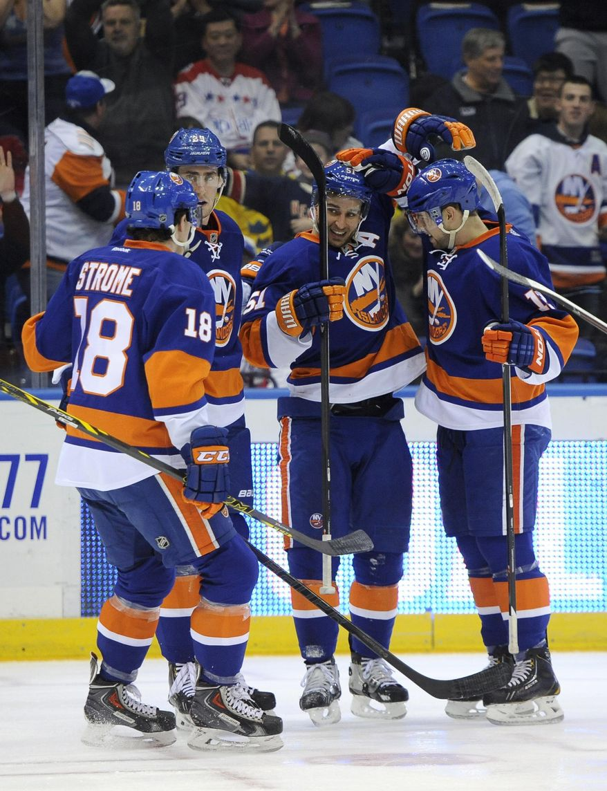 New York Islanders' Ryan Strome (18), Brock Nelson (29), Frans Nielsen (51) and Josh Bailey (12) celebrate Nielsen's goal against the Washington Capitals in the second period of an NHL hockey game on Saturday, April 5, 2014, in Uniondale, N.Y. (AP Photo/Kathy Kmonicek)