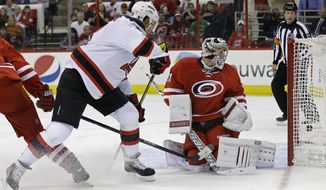New Jersey Devils' Dainius Zubrus, left, of Lithuania, scores against Carolina Hurricanes' goalie Anton Khudobin, of Kazakhstan, during the first period of an NHL hockey game in Raleigh, N.C., Saturday, April 5, 2014. (AP Photo/Gerry Broome)