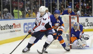 Washington Capitals' Nicklas Backstrom (19) controls the puck against New York Islanders' Travis Hamonic (3) as goalie Evgeni Nabokov (20) defends the net from behind   in the first period of an NHL hockey game on Saturday, April 5, 2014, in Uniondale, N.Y. (AP Photo/Kathy Kmonicek)
