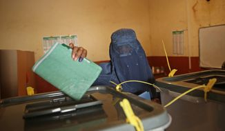 Afghan burqa-clad woman casts her vote at a polling station in Kabul, Afghanistan, Saturday, April 5, 2014. Afghans flocked to polling stations nationwide on Saturday, defying a threat of violence by the Taliban to cast ballots in what promises to be the nation's first democratic transfer of power. (AP Photo/Massoud Hossaini)