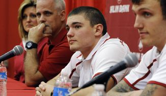 Indiana freshman football player Isaac Griffith, center, of Fort Wayne, Ind.; his parents, Kim and Shannon Griffith; and teammate Nick Stoner, right, attend a news conference along with another teammate, Ty Smith, at Memorial Stadium in Bloomington, Ind. Saturday, April 5, 2014. Three people pulled Griffiths out of a rip current off the Florida coast during spring break. (AP Photo/The Herald-Times, Chris Howell)