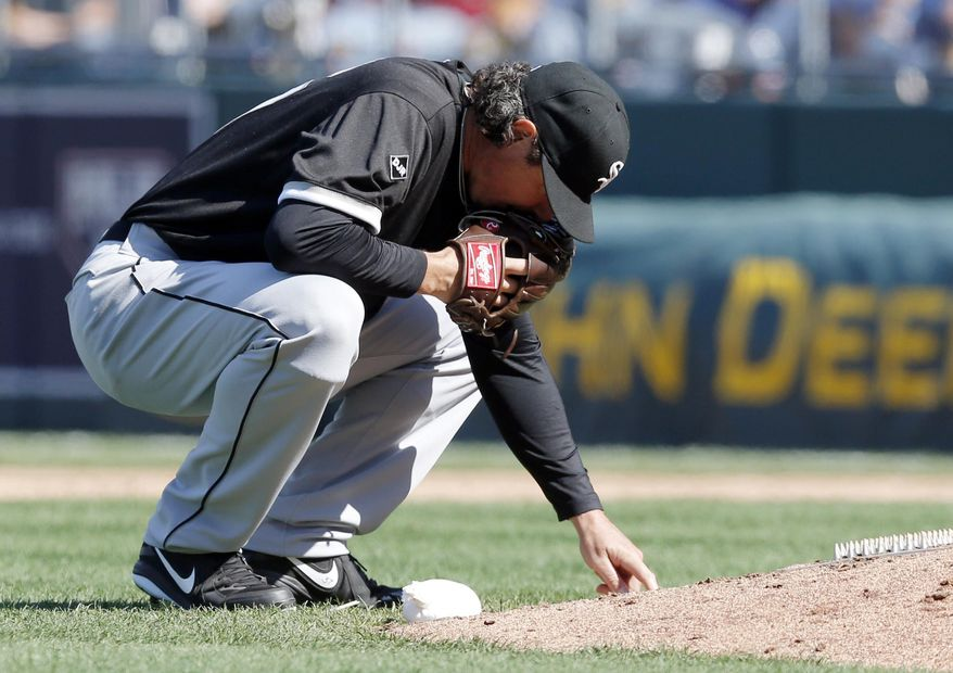 Chicago White Sox relief pitcher Scott Downs draws in the dirt behind the mound during the eighth inning of a baseball game against the Kansas City Royals at Kauffman Stadium in Kansas City, Mo., Saturday, April 5, 2014. The Royals won 4-3. (AP Photo/Orlin Wagner)