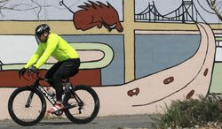 In this April 1, 2014 photo, a cyclist rides past a mural at Riverfront Park in North Little Rock, Ark. Arkansas has kicked off a series of public meetings on developing the first statewide bicycle and pedestrian plan in 15 years. (AP Photo/Arkansas Democrat-Gazette, Benjamin Krain)
