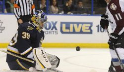 St. Louis Blues' goalie Ryan Miller (39) blocks a shot by Colorado Avalanche's Jamie McGinn (11) during the first period of an NHL hockey game, Saturday, April 5, 2014, in St. Louis. (AP Photo/Bill Boyce)