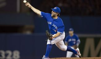 Toronto Blue Jays starting pitcher R.A. Dickey delivers a pitch during the fourth inning of a baseball game against the New York Yankees in Toronto on Saturday, April 5, 2014. (AP Photo/The Canadian Press, Peter Power)