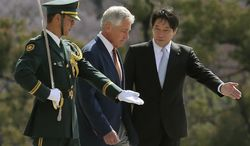 U.S. Secretary of Defense Chuck Hagel, center, is escorted by his Japanese counterpart Itsunori Onodera, right, as they inspect an honor guard at the Defense Ministry in Tokyo, Sunday, April 6, 2014. Against the backdrop of Russia's takeover of Ukraine's Crimean region, Hagel said Saturday he will convey to Japanese leaders that the U.S. is strongly committed to protecting their country's security. (AP Photo/Eugene Hoshiko)