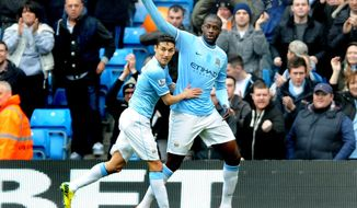 Manchester City's Yaya Toure, right, celebrates with teammate Jesus Navas after scoring from the penalty spot against Southampton during the English Premier League soccer match between Manchester City and Southampton at The Etihad Stadium, Manchester, England, Saturday, April  5, 2014.  (AP Photo/Rui Vieira)