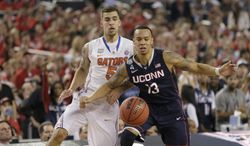 Connecticut guard Shabazz Napier, right, and Florida guard Scottie Wilbekin eye a loose ball during the second half of an NCAA Final Four tournament college basketball semifinal game Saturday, April 5, 2014, in Arlington, Texas. Connecticut won 63-53. (AP Photo/Charlie Neibergall)