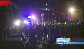 This video image provided by KEYT-TV shows a crowd confronting police at a disturbance Saturday April 5, 2014, during a weekend college party in Southern California that devolved into a street brawl. About 100 people were arrested and at least 44 people were taken to the hospital. (AP Photo/KEYT-TV)