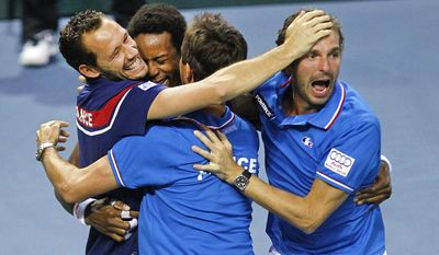 France's Gael Monfils celebrates with teammates Michael llodra, left, and Julien Benneteau, right, after winning his singles match against German player Peter Gojowczyk, in the quarterfinals of the Davis Cup in Nancy, eastern France, Sunday April 6, 2014. France qualifies for the semifinals with a 3-2 score.(AP Photo/Remy de la Mauviniere)