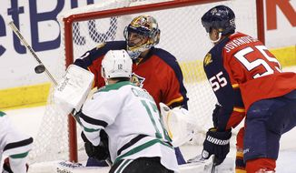 Florida Panthers goalie Roberto Luongo (1) blocks a shot as teammate  Ed Jovanovski (55) helps defend during the second period of an NHL hockey game against the Dallas Stars in Sunrise, Fla., Sunday, April 6, 2014. (AP Photo/Terry Renna)