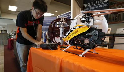 In this photo taken March 28, 2014, Ben Loh, a Ph.D. student from Oklahoma State University, works at a demonstration booth during a drone summit at Northeastern State University in Broken Arrow, Okla. (AP Photo/Tulsa World, Matt Barnard)  ONLINE OUT; KOTV OUT; KJRH OUT; KTUL OUT; KOKI OUT; KQCW OUT; KDOR OUT; TULSA OUT; TULSA ONLINE OUT
