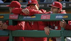 St. Louis Cardinals pitchers Lance Lynn, right, Shelby Miller, center, and Joe Kelly lean on the dugout railing during the ninth inning of a baseball game against the Pittsburgh Pirates in Pittsburgh Sunday, April 6, 2014. None of the three pitched in the 2-1 Pirates win. (AP Photo/Gene J. Puskar)