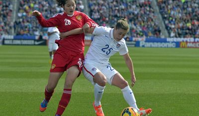 China midfielder Zhang Xin (28) and USA defender Megan Klingenberg (25) fight for the ball during the first half of an international friendly soccer match  in Commerce City, Colo., on Sunday, April 6, 2014. (AP Photo/Jack Dempsey)