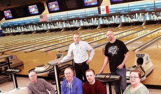 """This March 6, 2014 photo shows the Roseman family, front row from left, Rob Sr., Joe, Dusty and Linda, back row from left, Rob Jr. and Mike, pose for a photograph in Davenport, Iowa.  The family are the new owners of Leisure Lanes.  """"Everybody grew up in a bowling alley,"""" recalls Mike Roseman, who gave up his job as a route driver to manage the new family business. (AP Photo/The Quad City Times, Jeff Cook)"""
