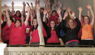 Red-shirted members of the Kansas National Education Association in the gallery of the Kansas House chamber raise their hands to show support for public schools as members leave for a break, Saturday, April 5, 2014, at the Statehouse in Topeka, Kan. The KNEA is the state's largest teachers' union and is protesting a proposal in an education funding bill to rewrite tenure rules. (AP Photo/John Hanna)