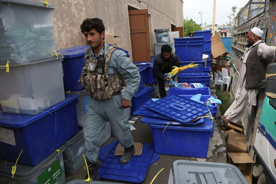 An Afghan policeman walks around as workers of the election commission office arrange ballot boxes in Jalalabad, east of Kabul, Afghanistan, Sunday. Across Afghanistan, voters turned out in droves Saturday to cast ballots in a crucial presidential election. The vote will decide who will replace President Hamid Karzai, who is barred constitutionally from seeking a third term. Partial results are expected as soon as Sunday. (Associated Press)