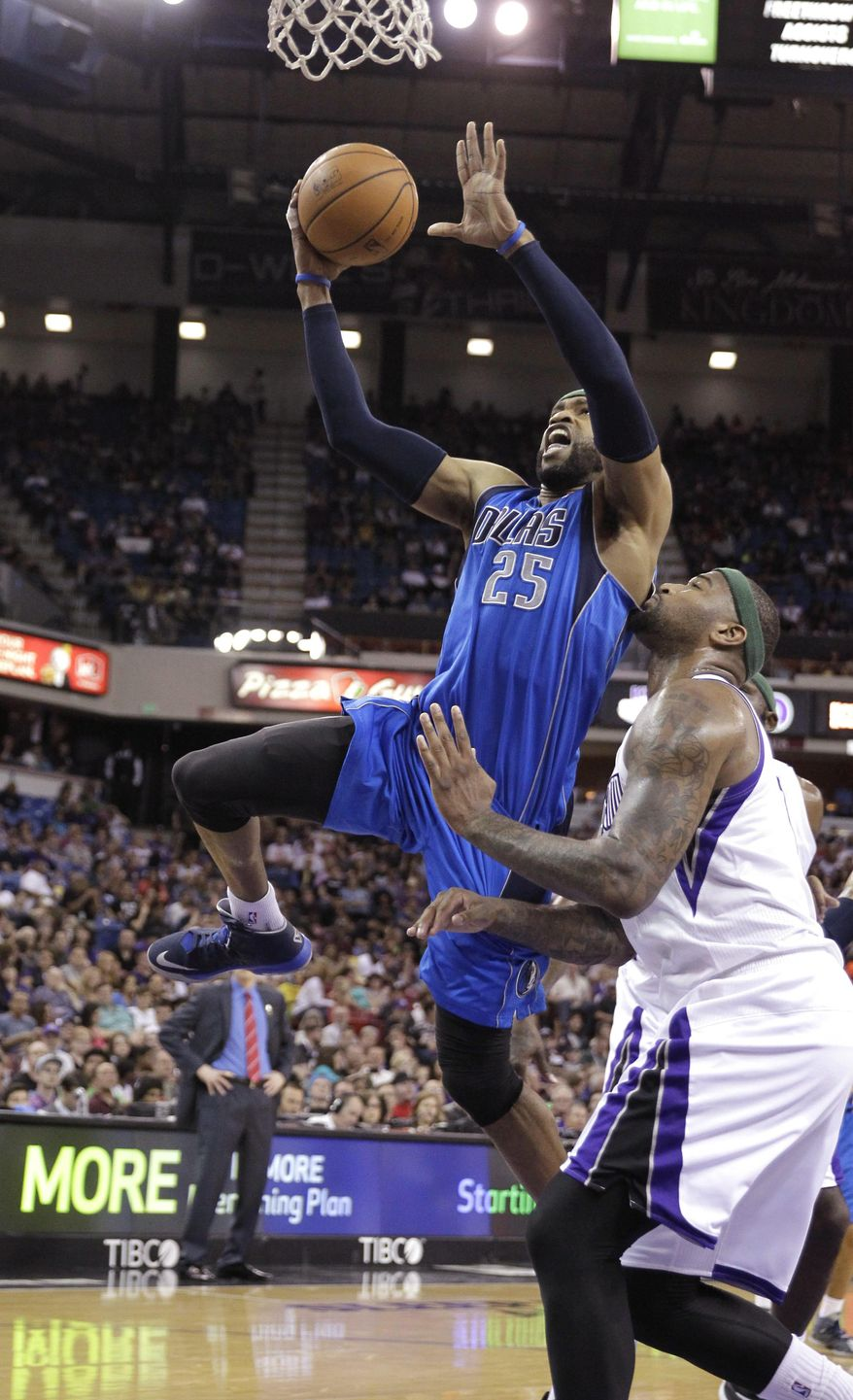 Dallas Mavericks guard Vince Carter, left, goes to the basket against Sacramento Kings center DeMarcus Cousins during the first quarter of an NBA basketball game, Sunday, April 6, 2014, in Sacramento, Calif.(AP Photo/Rich Pedroncelli)