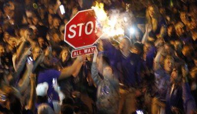 Kentucky fans wave a stop sign with a burning shirt near the University of Kentucky campus, Saturday, April 5, 2014, in Lexington, Ky., after Kentucky's 74-73 win over Wisconsin in the semifinals of the NCAA men's college basketball tournament Final Four in Arlington, Texas. (AP Photo/James Crisp)