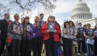 ** FILE ** In this Tuesday, April 1, 2014, file photo families of victims of a General Motors safety defects in small cars hold photos of their loved ones as they gather on the lawn on Capitol Hill in Washington. (AP Photo/J. Scott Applewhite, File)
