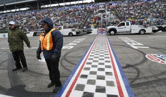 Track security guards Patrick Reyes, left, and Richard Gyure stand by the start-finish line as jet dryers blow dry the strait away before a rain delayed start of the NASCAR Sprint Cup Series auto race at Texas Motor Speedway in Fort Worth, Texas, Sunday, April 6, 2014. (AP Photo/Ralph Lauer)