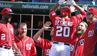 Washington Nationals' Ian Desmond (20) celebrates with Jayson Werth, second from right, and other teammates after hitting a game-winning solo home run during the seventh inning of a baseball game against the Atlanta Braves at Nationals Park, Sunday, April 6, 2014, in Washington. The Nationals won 2-1. (AP Photo/Alex Brandon)