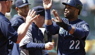 Seattle Mariners' Robinson Cano is congratulated after scoring against the Oakland Athletics in the third inning of a baseball game Sunday, April 6, 2014, in Oakland, Calif. Cano scored on a single by Justin Smoak. (AP Photo/Ben Margot)